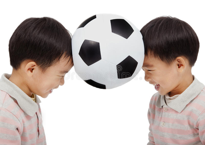 Happy kids holding a football. Above their head stock photos