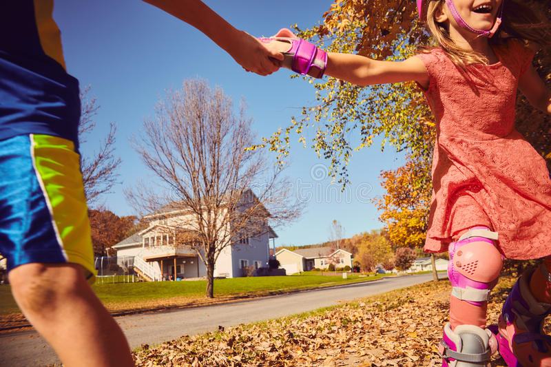 Happy kids holding hands while rollerskating stock image