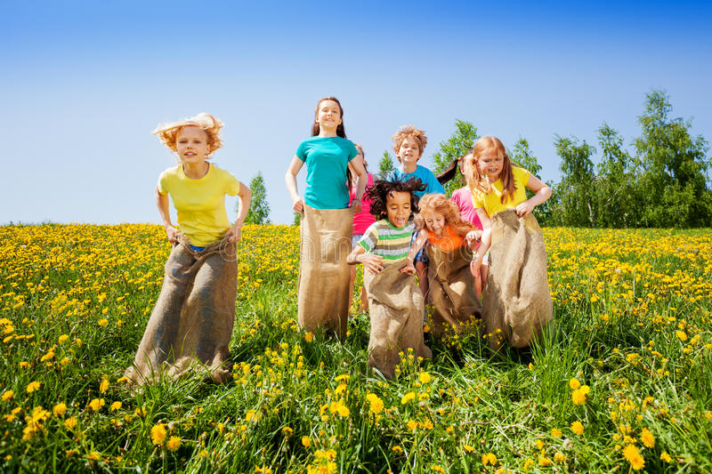 Happy kids jumping in sacks playing together. In summer royalty free stock image