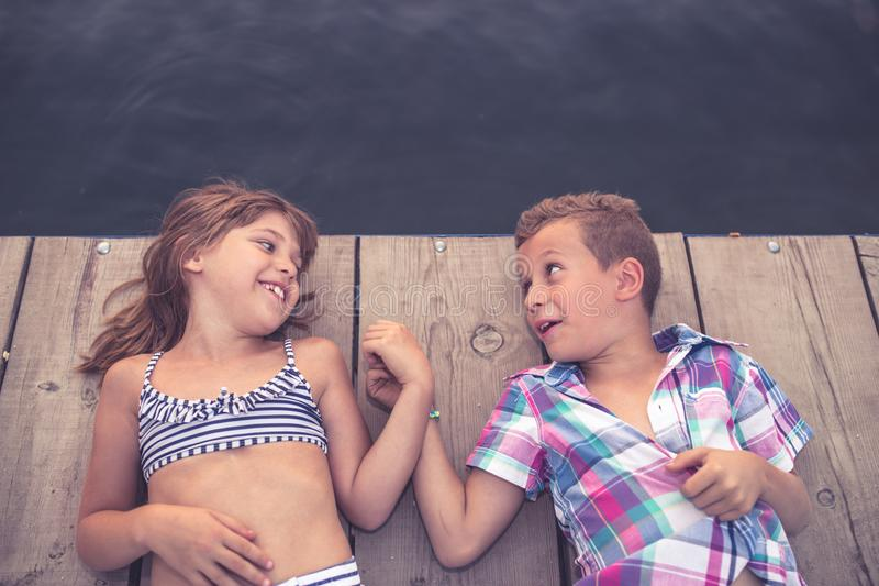 Happy kids lying on the wooden pier and holding hands royalty free stock images