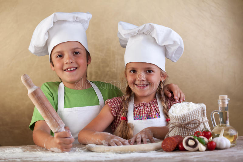 Happy kids making pizza togheter. Happy kids with chef hats making pizza togheter - stretching the dough royalty free stock photo
