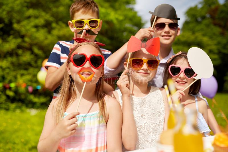 Happy kids with party props on birthday in summer. Holidays, childhood and celebration concept - happy kids with party props on birthday in summer garden royalty free stock image