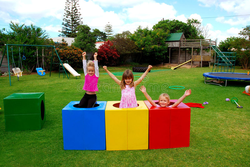 Happy kids on playground. Three beautiful caucasian girls with happy smiling facial expressions playing in colorful boxes and raising up their arms in the air on royalty free stock photo