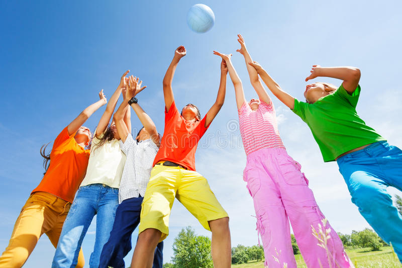 Happy kids playing with ball jumping in air. Over their heads outside stock image