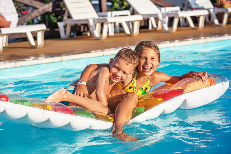 Happy kids playing in blue water of swimming pool. stock photo