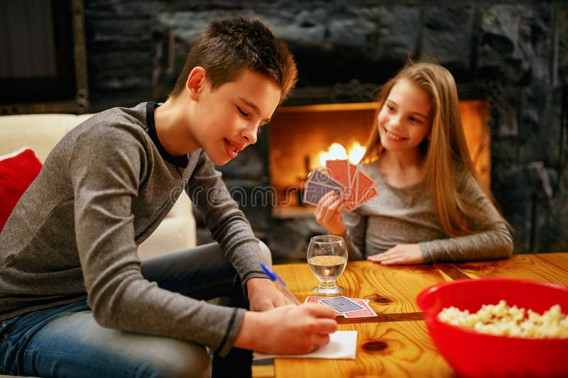 Kids playing card game at home stock photos