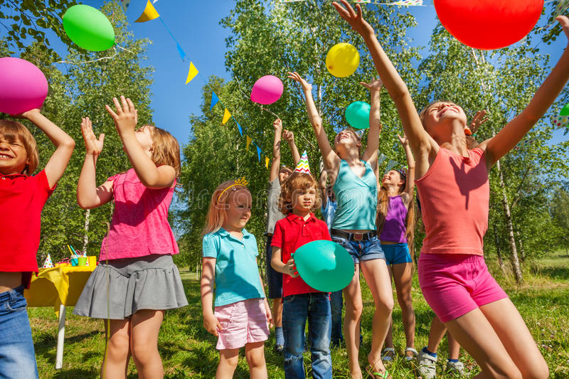 Happy kids playing and catching colorful balloons stock images