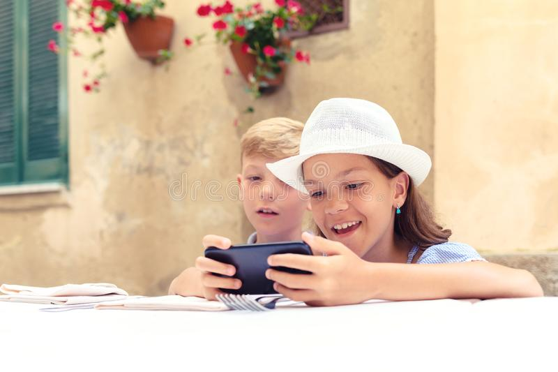 Happy kids playing with mom's smartphone waiting for food at restaurant royalty free stock images