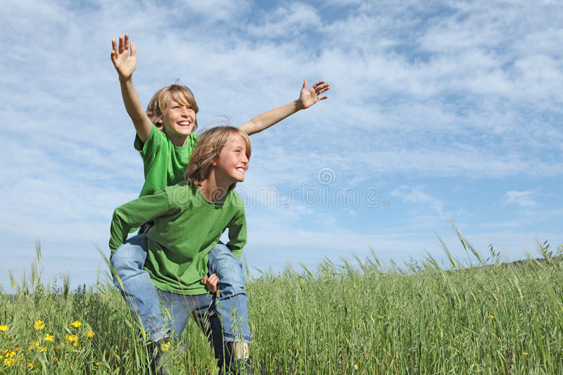 Happy kids playing piggyback race. Happy smiling kids or children playing piggyback race outdoors in summer camp stock photo