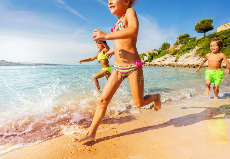 Happy kids playing racing games on the beach royalty free stock image