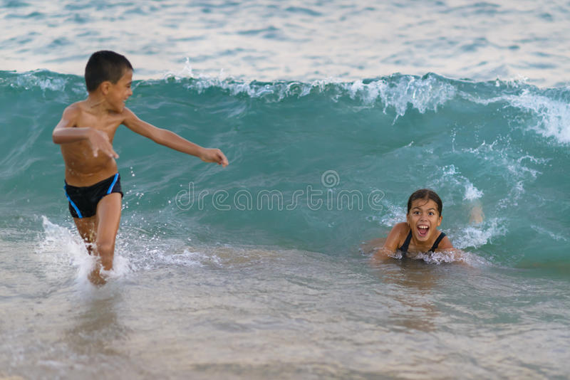 Happy Kids Playing at Sea. Big wave coming on them royalty free stock images