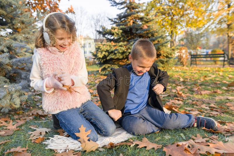 Happy kids playing and sitting on yellow leaves stock image