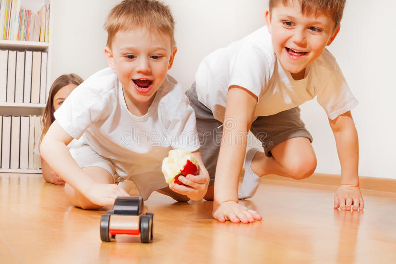 Happy kids playing with wooden toy car at floor. Happy kids, two brothers, playing with wooden toy car at the floor, chasing each other stock image
