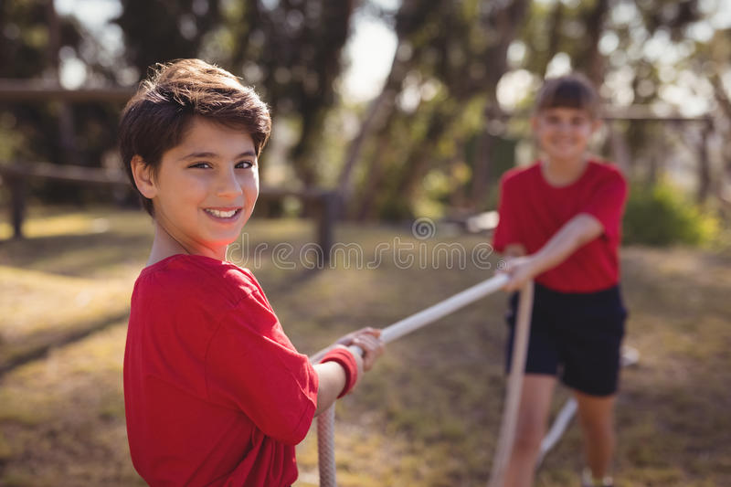 Happy kids practicing tug of war during obstacle course royalty free stock photography