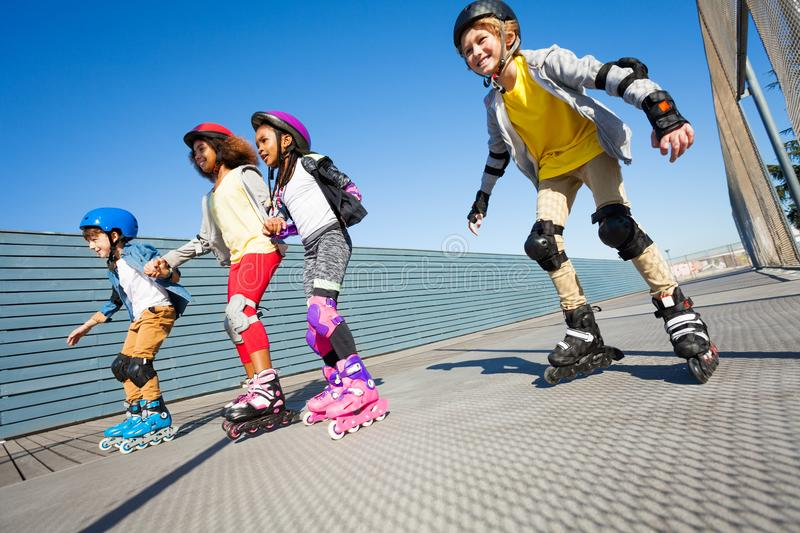 Happy kids rollerblading on the road at sunny day. Happy multiethnic kids rollerblading on the road with helmet and protective gear in summer royalty free stock photos