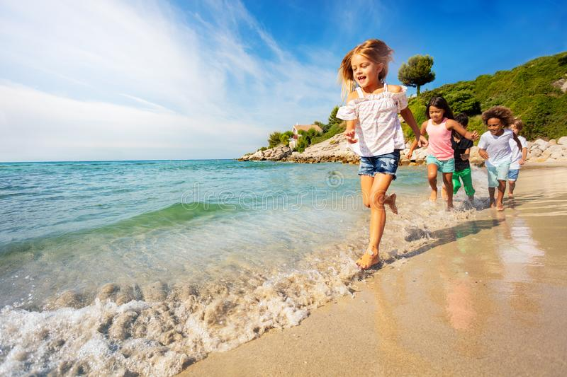 Happy kids running one after another on the beach royalty free stock photos