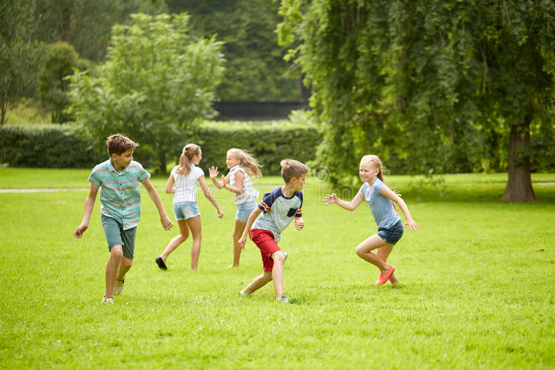 Happy kids running and playing game outdoors royalty free stock images
