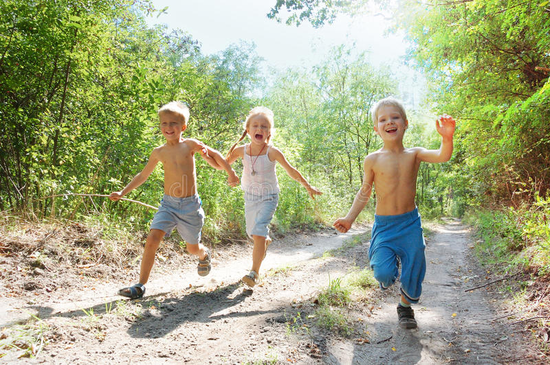 Happy kids running in the woods stock photo
