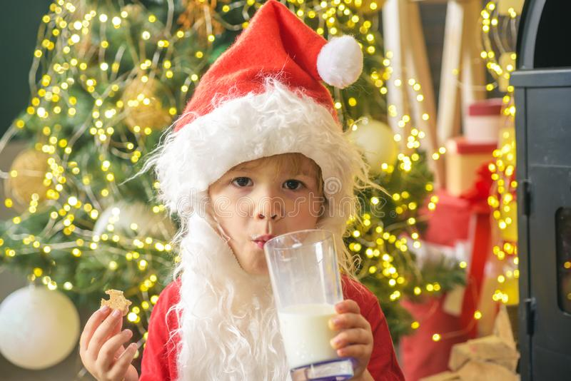 Happy kids Santa Claus with glass of milk and cookie. Santa Claus eating cookies and drinking milk on Christmas Eve royalty free stock photography