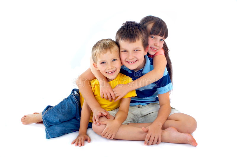 Happy kids sharing a hug. Three happy children hug each other, smiling as they pose for the camera