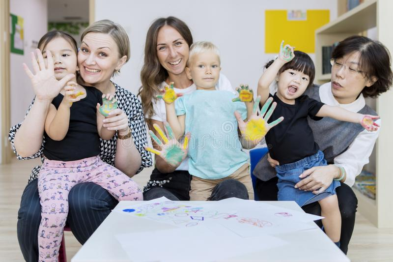Happy kids show painted palms with their mothers stock photo