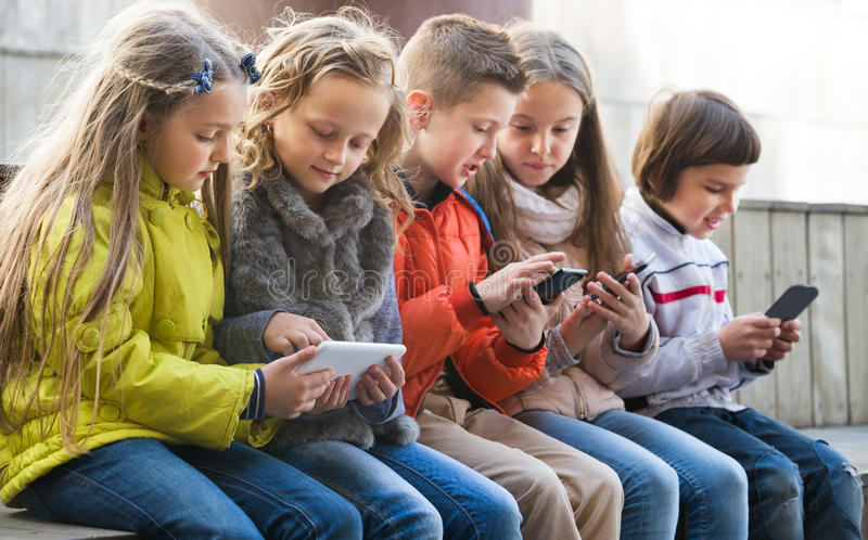 Happy kids sitting on bench with mobile devices royalty free stock images