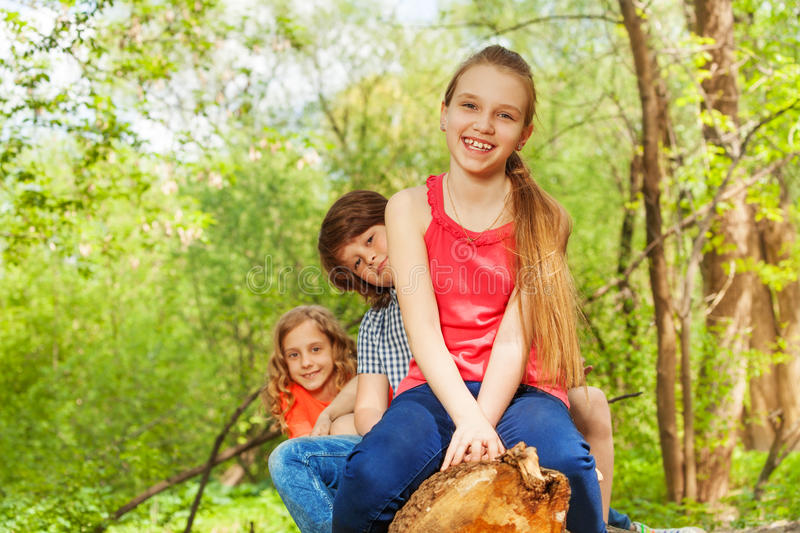 Happy kids sitting on a log in row stock photography