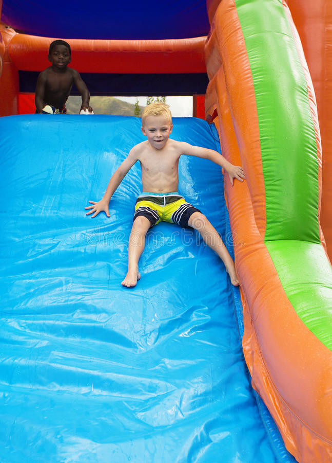 Happy kids sliding down an inflatable bounce house stock image