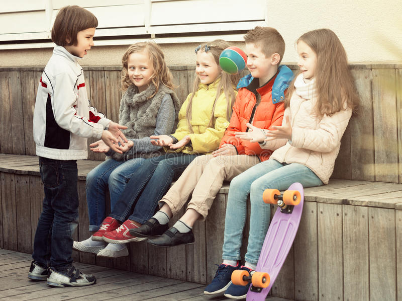 Happy kids with small ball playing in street. Happy kids with small ball playing in city street royalty free stock image