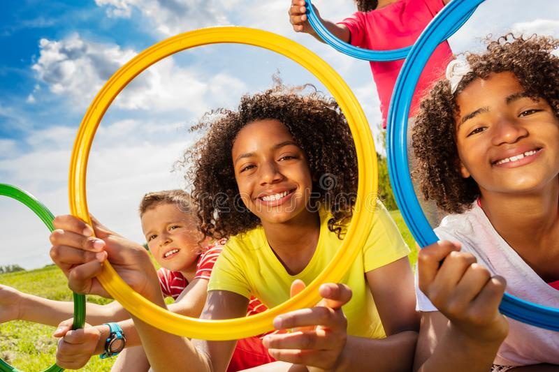Happy kids smile look through colorful hoops rings. Group of children boy and girls sit in the park with colorful hoops showing happy smiles royalty free stock images