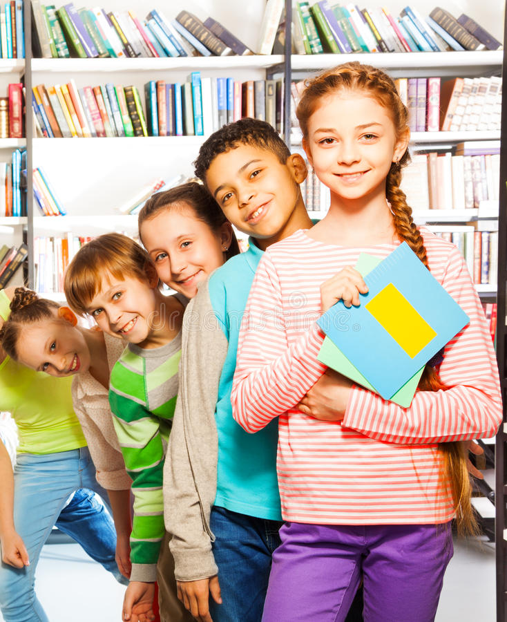 Happy Kids Standing In Row Inside Library Stock Photo
