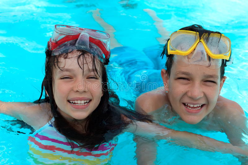 Happy kids swimming. A happy boy and a happy girl in a swimming pool with swimming goggles royalty free stock photos