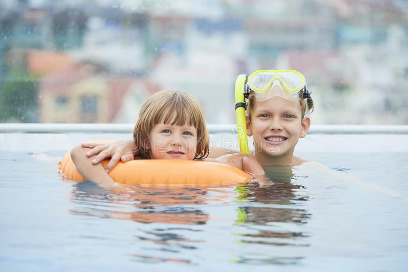 Happy kids in swimming pool stock photography