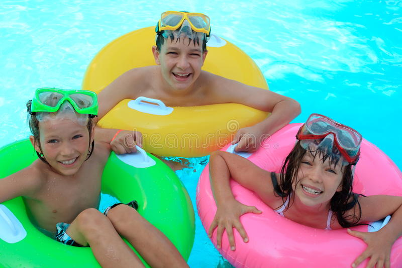 Happy kids in swimming pool. Three happy kids playing in a swimming pool with swimming rings stock photography