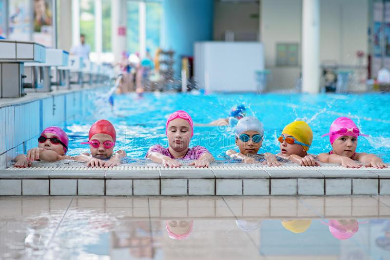 Happy kids at the swimming pool. young and successful swimmers pose. Happy kids at the swimming pool. young and successful swimmers pose royalty free stock images