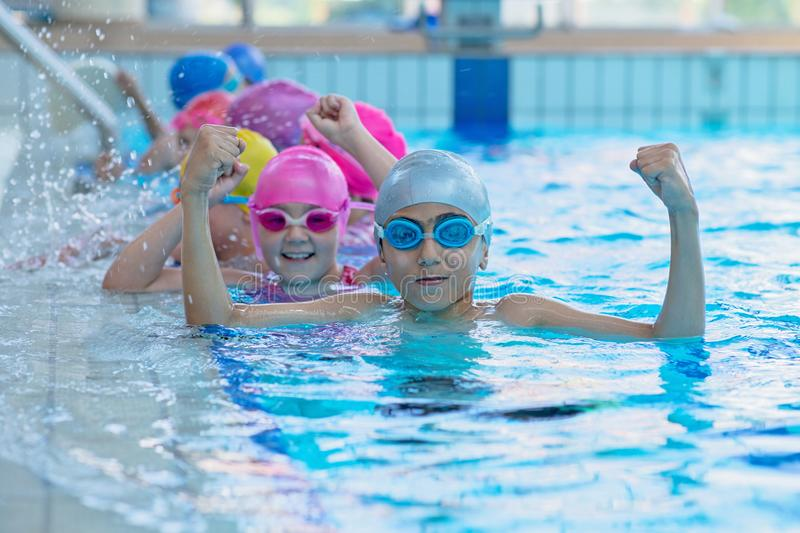 Happy kids at the swimming pool. young and successful swimmers pose. Happy kids at the swimming pool. young and successful swimmers pose royalty free stock photo