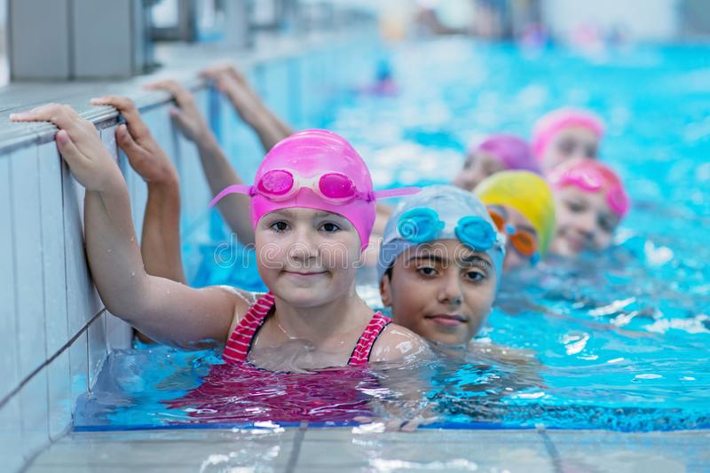 Happy kids at the swimming pool. young and successful swimmers pose. Happy kids at the swimming pool. young and successful swimmers pose stock image