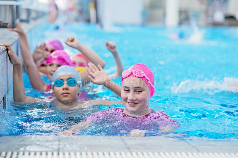 Happy kids at the swimming pool. young and successful swimmers pose. Happy kids at the swimming pool. young and successful swimmers pose royalty free stock photos