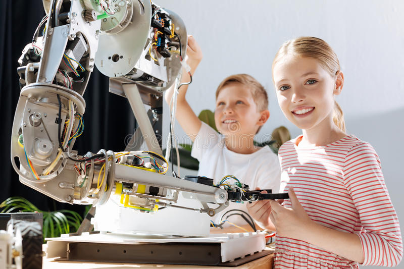 Happy kids taking part in the construction of robot stock images