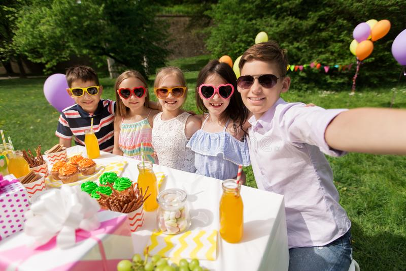 Happy kids taking selfie on birthday party. Holidays, childhood and technology concept - happy kids in sunglasses taking selfie on birthday party at summer stock images