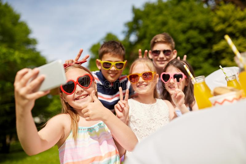 Happy kids taking selfie on birthday party. Holidays, childhood and technology concept - happy kids in sunglasses taking selfie on birthday party at summer royalty free stock photography
