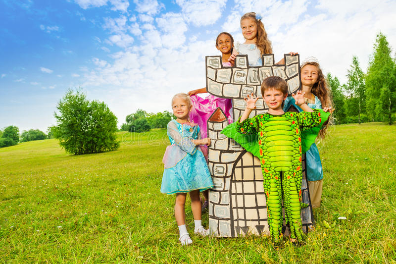 Happy kids in theatric costumes play around tower stock images