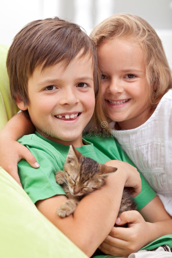 Happy kids with their new pet - a little kitten. Happy kids holding their new pet - a little kitten asleep in their arms royalty free stock photo