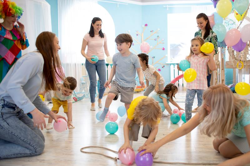 Happy kids and their parents entertain and have fun with color balloon on birthday party stock photography