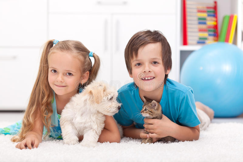 Happy kids with their pets - a dog and a kitten. Laying on the floor