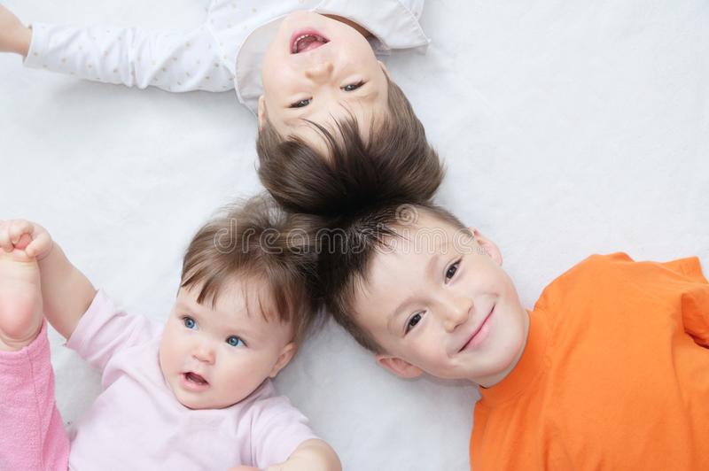 Happy kids, three laughing children different ages lying, portrait of boy, little girl and baby girl, happiness in childhood stock photo