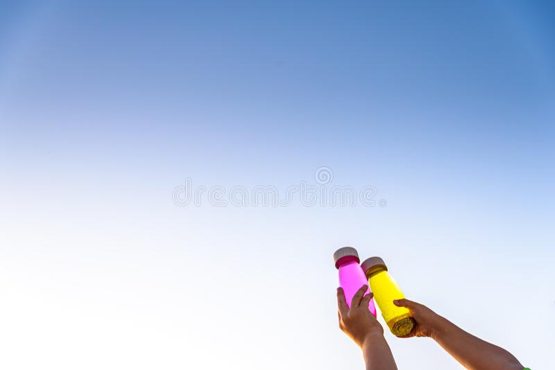 Happy kids toasting with toy bottles of vibrant colors with blue sky background stock image