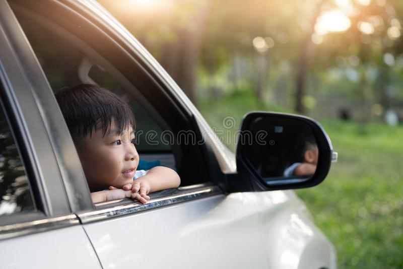 Happy kids travel by the car, Little boy peeks out of the car in the sunset stock photo