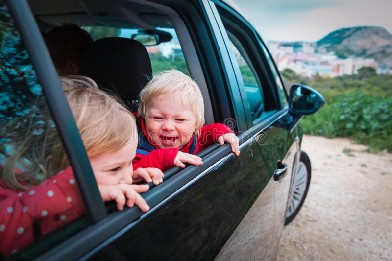 Happy kids travel by car on road in nature stock photos