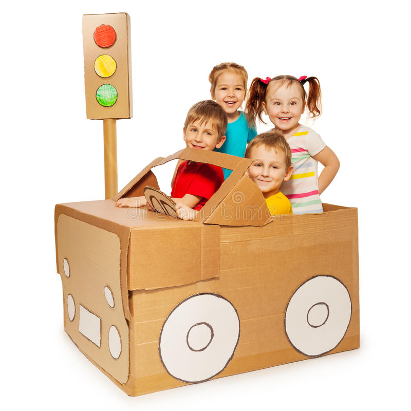 Happy kids travelling by cardboard car stock photos